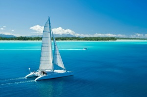 MAGIC Cat sailing by white sand beach